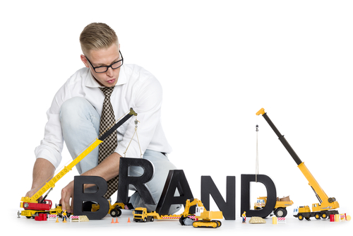 Focused businessman building the word brand